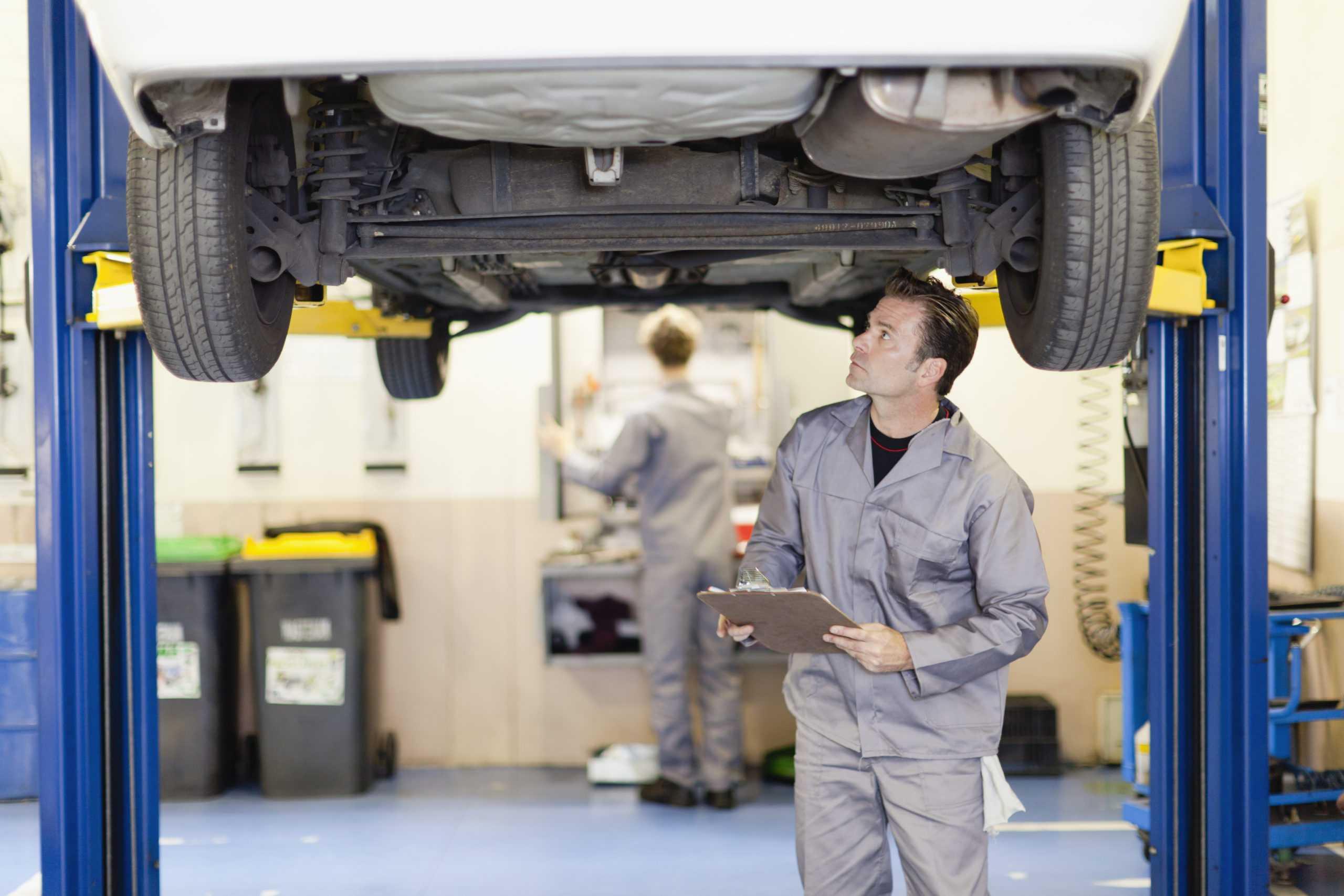 Mecánico examinando los bajos del coche